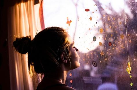 menina olhando na janela